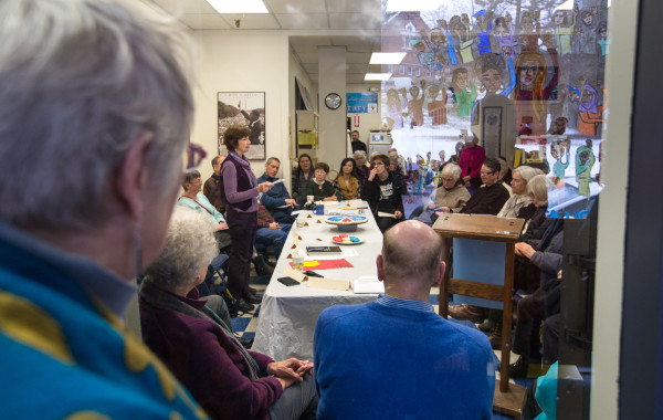 People listen as Mary Ellen Quinn, co-coordinator of Pax Christi Maine, speaks during a &quotPeople's Inauguration&quot on Friday at the Peace & Justice Center of Eastern Maine in Bangor.