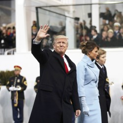 President Donald Trump (left) waves while walking with wife Melania during the Inaugural Parade on Friday in Washington. Trump was sworn in earlier as the 45th president of the United States.
