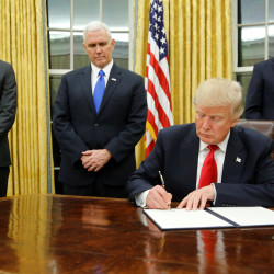 President Donald Trump, flanked by Senior Advisor Jared Kushner (standing, left to right), Vice President Mike Pence and Staff Secretary Rob Porter welcomes reporters into the Oval Office for him to sign his first executive orders at the White House in Washington, Jan. 20, 2017.