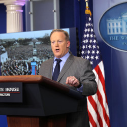Press Secretary Sean Spicer delivers a statement while a television screen show a picture of President Donald Trump's inauguration at the press briefing room of the White House in Washington, Jan. 21, 2017.
