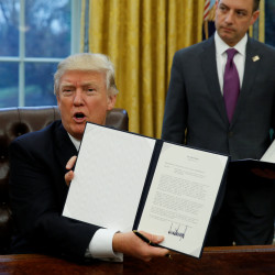 President Donald Trump holds up the executive order on withdrawal from the Trans-Pacific Partnership after signing it as White House Chief of Staff Reince Priebus stands at his side in the Oval Office of the White House in Washington, Jan. 23, 2017.