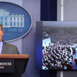 Press Secretary Sean Spicer delivers a statement while television screen show a picture of U.S. President Donald Trump's inauguration at the press briefing room of the White House in Washington U.S., Jan. 21, 2017.