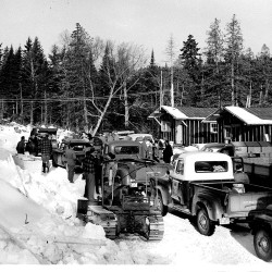 The first Maine-Quebec winter caravan heading through the forests of western Aroostook County can be seen in 1957.