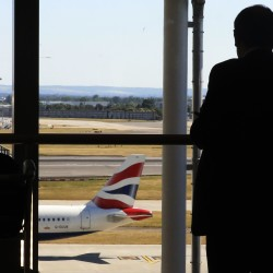 A passenger watches airplanes from Terminal 3 at Heathrow Airport in London, July 3, 2014.