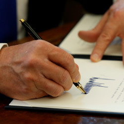 President Donald Trump signs an executive order to advance construction of the Keystone XL pipeline at the White House in Washington, Jan. 24, 2017.