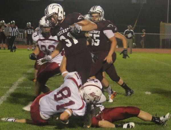 Foxcroft's Billy Brock (center) is wrapped up by the Orono defense as Foxcroft's Johnny Labree looks on during their preseason football game on Friday at Oakes Field in Dover-Foxcroft.