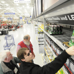 Brian Papineau (foreground) of Old Town reaches for an LED light as Sid Sinclair (left), a field representative with the Efficiency Maine lighting program, and Lowe's customer service associate Willy Willette (background) help him make his choice at the new Lowe's Home Improvement store on Springer Drive in Bangor.