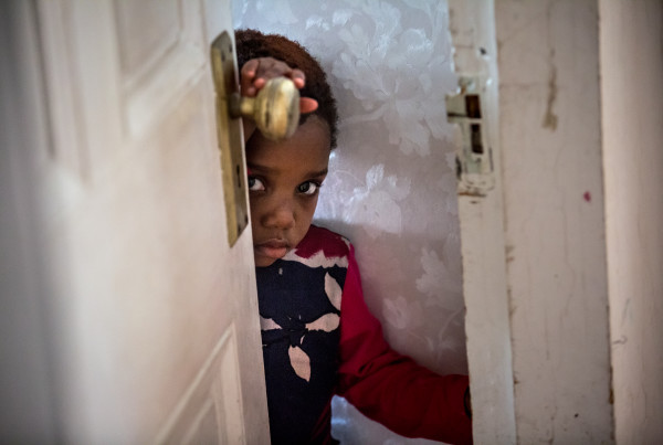 Josephine Jordan, 3, peers out from the doorway leading to her family's front hall after coming down from the upstairs to investigate the sound of visitors in December 2016. When they first arrived in Thomaston and the older Kaluta children started going to school, Josephine would get ready, put on a backpack, and try to sneak out with the rest of the group. She spends most of her time inside the family's Thomaston home, as the Kalutas' don't have any form of transportation to leave the town.