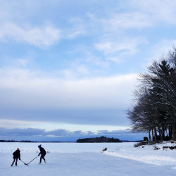 Caleigh Dareies (right), 9, watches as Aiden Rand (center), 13, plays a game of pond hockey with sister, Lily Rand, 9, on Pushaw Lake in Orono in December.