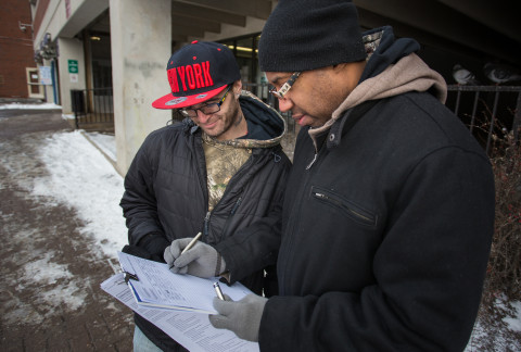 Ralph Tripp, 32, of Bangor and Maurice Gunn coordinate on a signature-gathering effort on a 2016 referendum for a York County casino outside the garage at Pickering Square in Bangor in this January 2016 file photo.