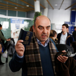 Fuad Sharef Suleman shows his passport to the media after President Donald Trump's decision to temporarily bar travelers from seven countries, including Iraq, at Erbil International Airport, Iraq, Jan. 29, 2017.