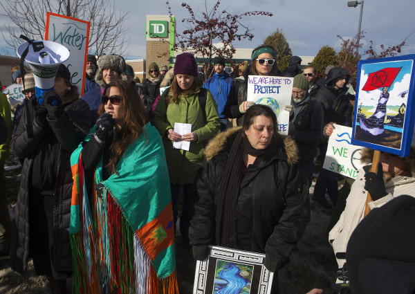 Sherri Mitchell (left) talks to members of the community as they gather in front of TD Bank in Bangor Saturday during a rally to oppose the Dakota Access Pipeline.