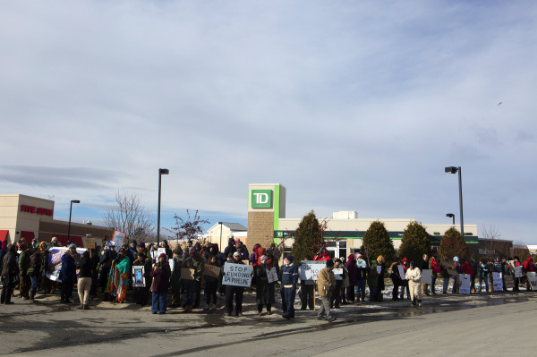 Members of the community gather in front of TD Bank in Bangor Saturday during a rally to oppose the Dakota Access Pipeline.