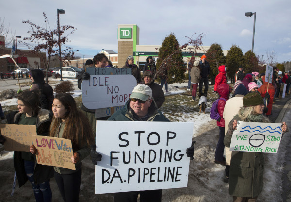 Sherman Hoyt (center) holds his sign in front of TD Bank in Bangor Saturday during a rally to oppose the Dakota Access Pipeline.