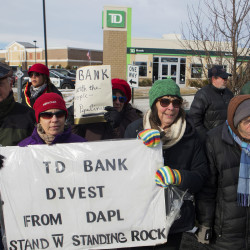 Karen Blaisdell (left) and Meredith Bruskin hold a sign in front of TD Bank in Bangor Saturday during a rally to oppose the Dakota Access Pipeline.