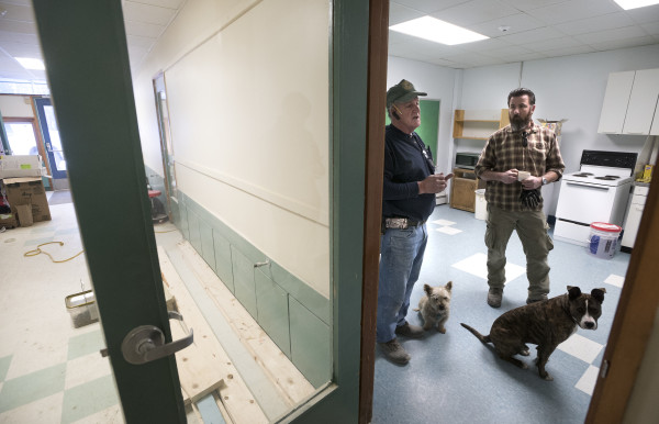 Jake Chambers (left), owner of Adult Family Care Homes of Maine, talks with his son Tom Chambers during a tour of the former Frankfort Elementary School on Tuesday in Frankfort. The building is being converted into an assisted living facility.