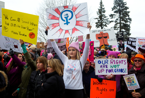 Elizabeth Robbins (center) of Bangor holds up her sign during the Women's March on Maine outside the Burton M. Cross building at the Maine State House in Augusta on Saturday. The national rally was in support of women's rights, civil liberties and protection of the planet.