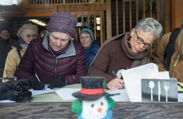 Donna Gilbert (left) of Winterport and Jo DeVries of Holden sign a petition at Java Joe's before marching up Harlow Street on Tuesday morning to visit the Bangor office of Sen. Susan Collins as part of a statewide campaign across the state protesting her support for and introduction of Sen. Jeff Sessions for Attorney General.