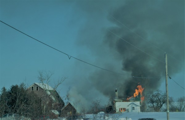 Flames and dark smoke rise from a house fire at 250 Hare Road in Monticello on Monday.
