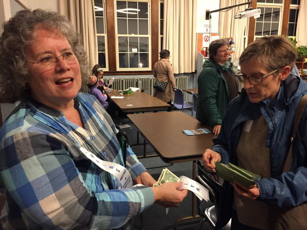 Mary Beth Taylor of Poland, Maine sells ribbons at a Maine March organizational meeting Wednesday night in Portland.