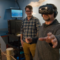 Neil Greenberg, right, assistant director of aquatic operations at the Aquaculture Research Institute, dons a virtual reality headset to become immersed in a 360-degree, panoramic, 3-D fish farm. University of Maine senior Eric Morrison, center, developed the virtual reality component.