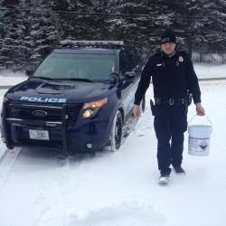 Madawaska Police Officer Matt Derosier delivers a bucket of salt to an elderly residents home in Madawaska on Thursday morning.
