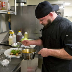 Dustin Cyr drizzles the glaze on the sweet chili-sesame glaze scallops at Novio's Bistro in Bangor Wednesday.