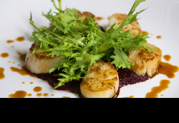 he sweet chili-sesame glaze scallops are seen at Novio's Bistro in Bangor.