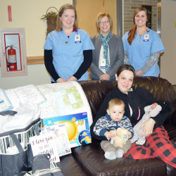 Presque Isle's Lorissa Ferrin, with her sons Oliver and newborn Alexander, is presented a number of gifts by the staff in the TAMC Women and Children's unit in honor of Alexander's arrival as the first baby born at TAMC in 2017.  Presenting the gifts are (standing, left to right) Deidre Clark, RN; Mary Hamilton, CNM; and Brittney White, RN.