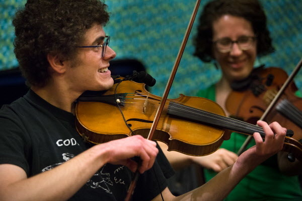 Fiddlers Eric Goodman (left) and Emily Troll provide the musical propulsion at the Portland Intown Contra Dance on Thursday night at the State Street Church. The weekly dance always features live musicians from around New England.