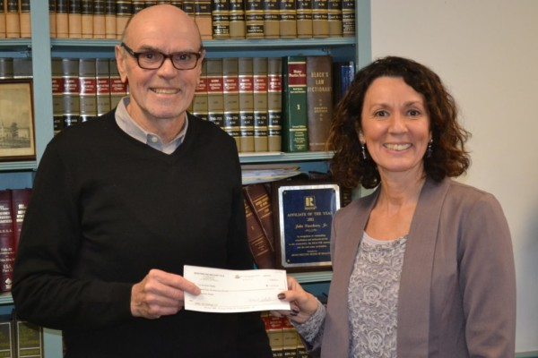 Steve Barndollar, of JSJ Holdings LLC, presents Sherri Dunbar, of Tim Dunham Realty, a check for the former Wiscasset Primary School at the Merrymeeting Midcoast Title LLC in Brunswick on Monday, Jan. 30.