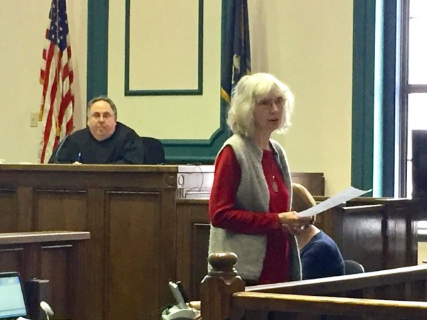With Justice Daniel Billings looking on, Connie Jenkins, 68, of Orono, a retired nurse practitioner and psychotherapist, speaks to the jury during the trial of 10 protesters arrested during a June 2016 protest outside Bath Iron Works.