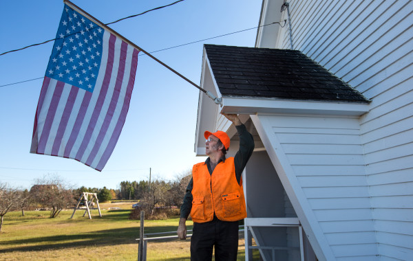 Steve Sherman, first assessor of Oxbow Plantation, hangs the American flag outside the community center, where residents came Nov. 8, 2016, to vote in favor of dissolving their local government.