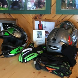 The latest in snowmobile gear rests on a table in front of historic photos of the Allagash region at Two Rivers Lunch. The small, northern Maine community is becoming a popular destination for sledders thanks to consistent snow cover.