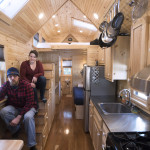 Nic Ledoux (left) and his wife, Robin Bienenstock, recently sit in their tiny home that is parked at a campground in Freeport. They bought the home last year and decided to come to Maine for their first winter.