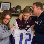 """Chris Fickett Sr. (right) kisses the hair of Chris Jr. (center), his youngest son, as he and mother Tina Fickett greet the approaching family dog as the family gathered in front of the urn of their son and brother Harold """"Thomas"""" Fickett to show off his old football jersey from John Bapst High School on Thursday in Clifton."""