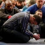 A man mourns during a funeral ceremony for three of the victims of the deadly shooting of the Quebec Islamic Cultural Centre at the Congress Center in Quebec City on Feb. 3.