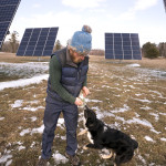 Carl Johanson, 26, plays with his dog while talking about the recently installed large solar array at Goranson Farm in Dresden. Johanson's parents own the farm and were the driving force behind the project that is to cover the energy needs at the 80-acre organic farm.