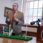 Gov. Paul LePage uses a model of a home selling solar power to the electric grid during a press conference at the State House to decry a recent decision by the Public Utilities Commission that he says will force Maine ratepayers to subsidize the solar industry.