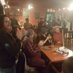 "Zachary Fowler (right) places his hands on his head while he watches the finale of History Channel's ""Alone"" survival show during a viewing party Thursday at Threshers Brewing Co. in Searsmont. Fowler won the show."