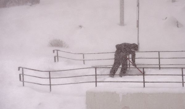 A man shovels snow from a walkway in blizzard conditions in downtown Bangor Monday.