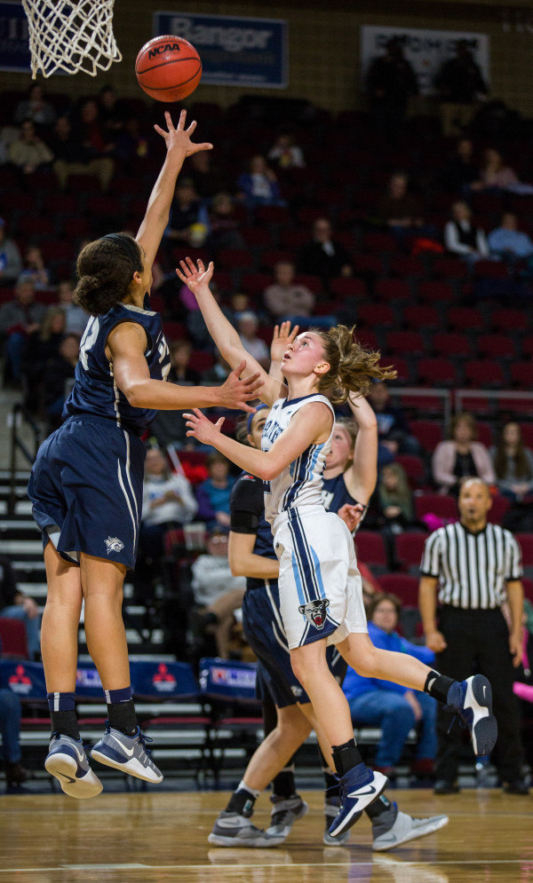 University of Maine's Sigi Koizar (right) goes for the shot but is blocked by University of New Hampshire's Carlie Pogue during their game at the Cross Insurance Center in Bangor on Wednesday.
