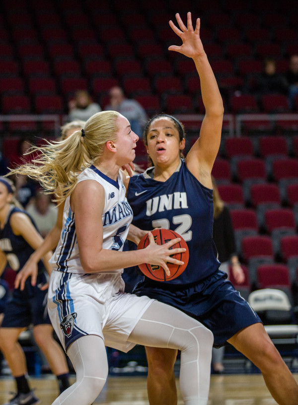 University of Maine's Tihana Stojsavljevic (left) looks to pass but is blocked by University of New Hampshire's Carlie Pogue during their game at the Cross Insurance Center in Bangor on Wednesday.