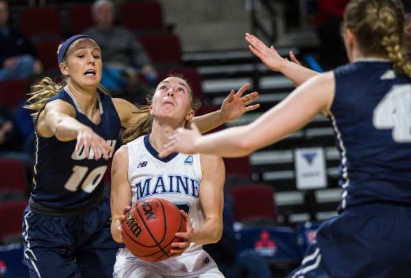 University of New Hampshire's Aliza Simpson (left) reaches to block a shot by University of Maine's Sigi Koizar during their game at the Cross Insurance Center in Bangor on Wednesday.