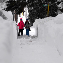 Friends Lily Bernier (left) and Abby Bergmark, fourth graders at the Mary Snow School, walk down a plowed sidewalk on Linden Street in Bangor on their way to school Thursday morning