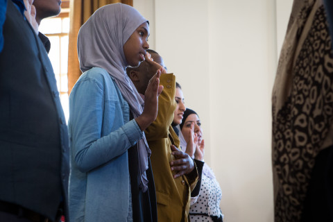 Refugees take an oath of allegiance at City Hall in Portland as they become naturalized U.S. citizens.
