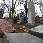 Spencer Pensoneau (left) Ron Klump and Philip Weiss of Rosenbloom Monument Co. re-set stones at Chesed Shel Emeth Cemetery in University City on Tuesday, where almost 200 gravestones were vandalized over the weekend in St. Louis.