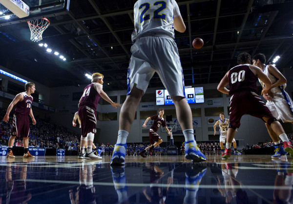 Hermon's Cody Hawes (center) throws the ball back into play to teammate Hermon's Tyler Hawes during their Class B boys basketball semifinal game against Orono at the Cross Insurance Center in Bangor Wednesday.