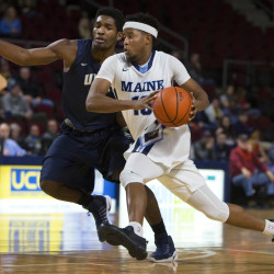 University of Maine's Wes Myers (right) drives the lane past University of New Hampshire's Jaleen Smith during their basketball game at the Cross Insurance Center in Bangor on Jan. 19, 2017.