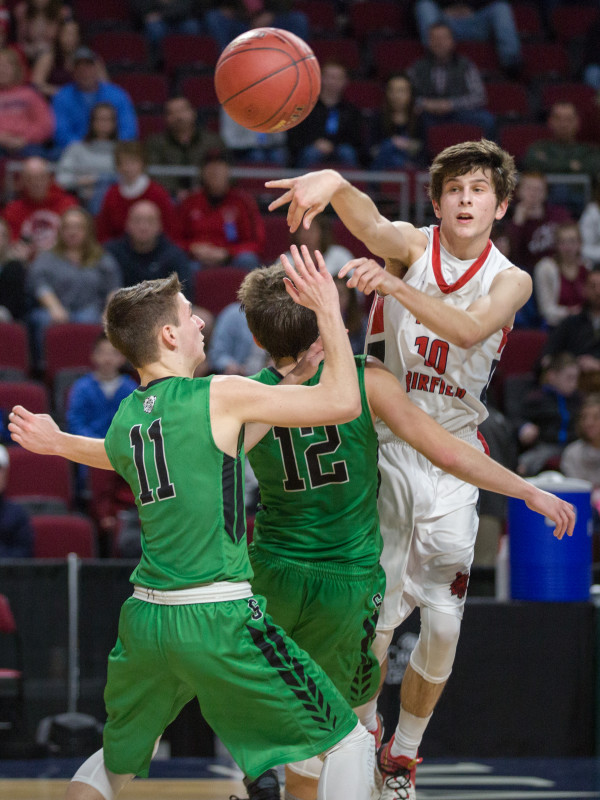 Fort Fairfield's Isaac Cyr (back right) passes over the heads of Schenck defensemen Christopher J. King (center) and Colby Hannan during their class C boys semifinal game at the Cross Insurance Center in Bangor on Friday afternoon.